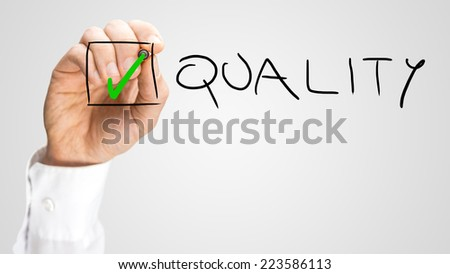 Hand Putting Small Green Check Inside Check Box for Quality. Isolated on Grey Background. - stock photo