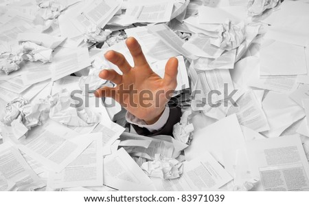 Hand reaches out from big heap of crumpled papers - stock photo