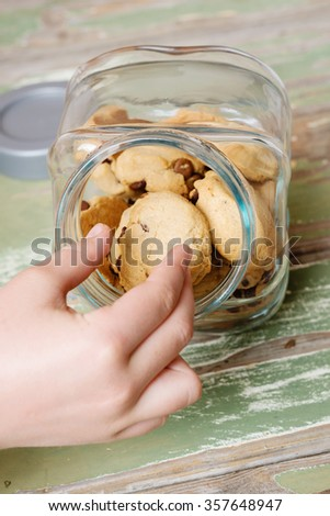 hand reaching for choc chip cookies in a jar - stock photo