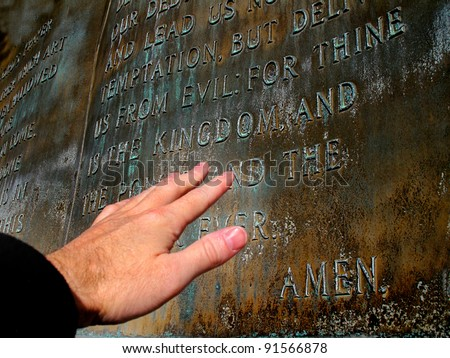 Hand reaching out to sculpture of the Lord's Prayer - stock photo