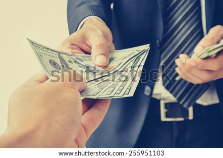 Hand receiving money, US dollars,  from business man - vintage (retro) style color effect - stock photo