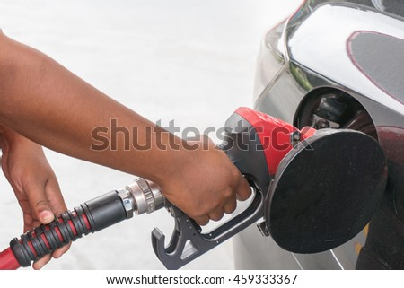 Hand refilling the car with fuel on a filling station  - stock photo