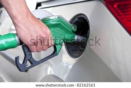 Hand, refuelling a passenger car, holding a green fuel pump - stock photo