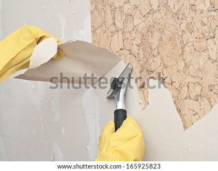 Hand removing wallpaper from wall  - stock photo