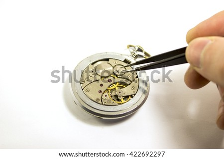 Hand repairs an old mechanical watch with white background - stock photo