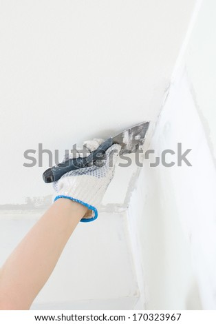 Hand repairs gypsum plasterboard frame with spackling paste - stock photo