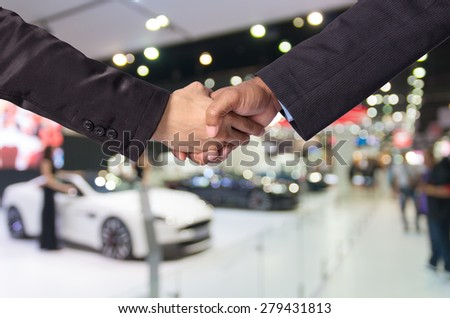 Hand shake between a businessman and a businesswoman on abstract blurred photo of motor show background - stock photo