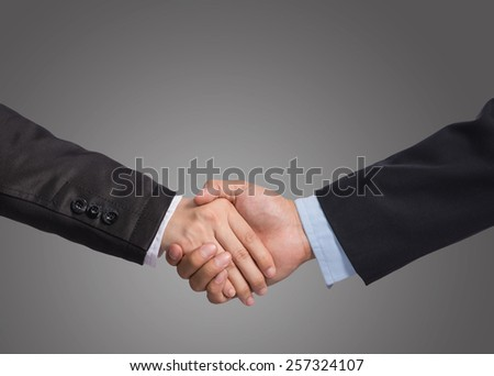 Hand shake between a businessman and a businesswoman on gray background, include clipping path - stock photo