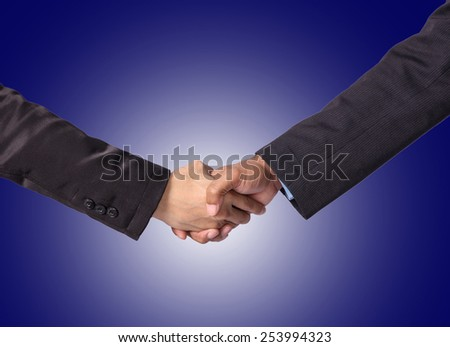 Hand shake between a businessman on dark blue background - stock photo