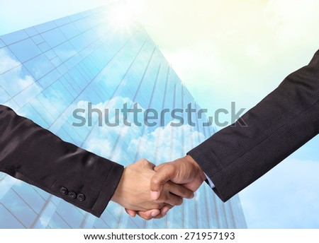 Hand shake between a businessman on Modern glass building with cloud background,Business concept - stock photo