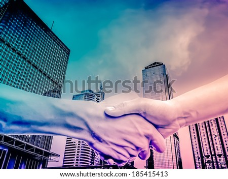 hand shake with modern urban city buildings skyscrapers - stock photo