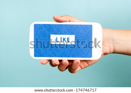 """Hand showing a horizontal paper mobile phone with """"like button"""" on blue background. - stock photo"""