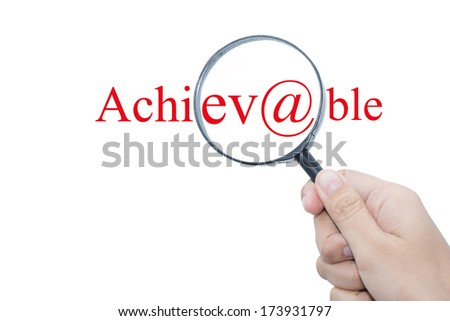 Hand Showing Achievable Word Through Magnifying Glass  - stock photo