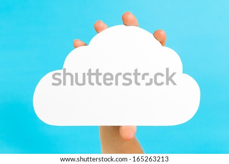 Hand showing an isolated white cloud, on vibrant blue background. Cloud computing and internet concept. - stock photo