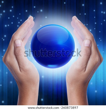 Hand showing blue crystal ball. - stock photo