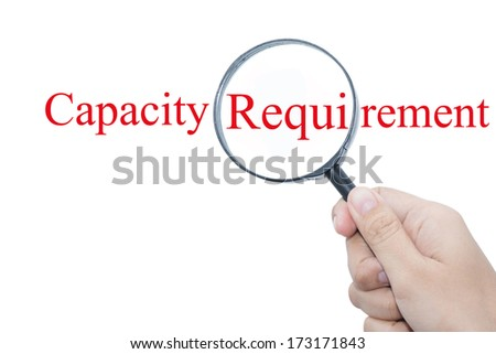 Hand Showing Capacity Requirement Word Through Magnifying Glass  - stock photo