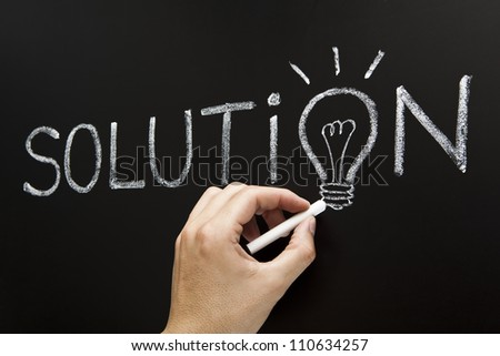 Hand showing chalk drawn light bulb on the place of the letter O in the word Solution on blackboard. - stock photo
