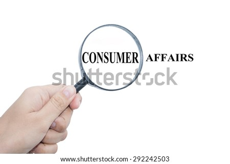 Hand Showing CONSUMER AFFAIRS Word Through Magnifying Glass  - stock photo