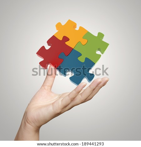 Hand showing 3d puzzle as concept - stock photo