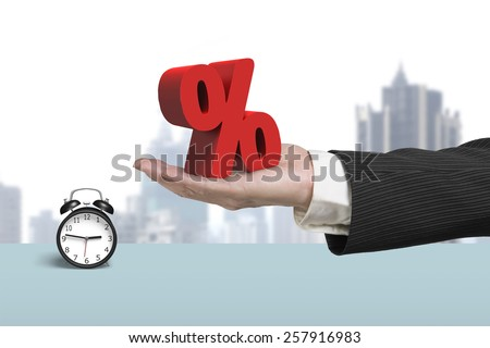 Hand showing 3D red percentage sign with alarm clock and cityscape background - stock photo