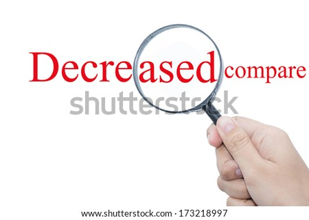 Hand Showing decreased compare Word Through Magnifying Glass  - stock photo