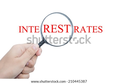Hand Showing INTEREST RATES Word Through Magnifying Glass - stock photo