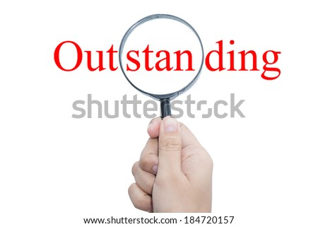 Hand Showing Outstanding Word Through Magnifying Glass  - stock photo
