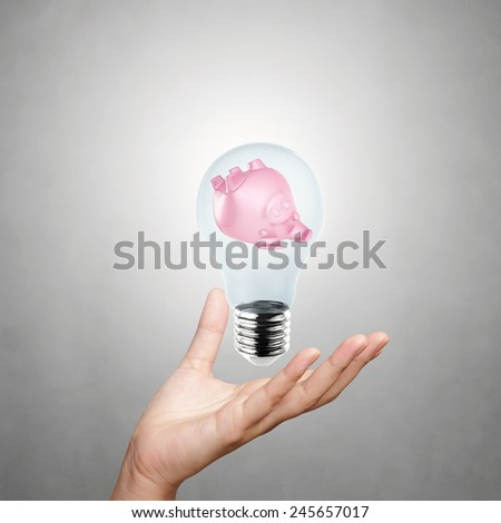 hand showing piggy bank with light bulb as concept - stock photo