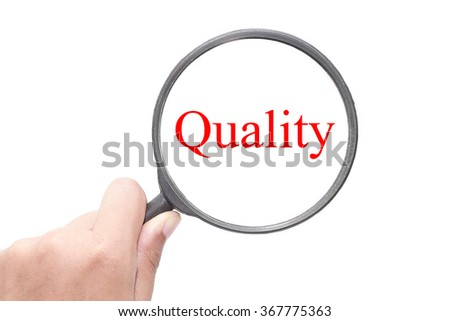 Hand showing Quality word through magnifying glass. Magnifying glass search concept. Isolated on white background. - stock photo