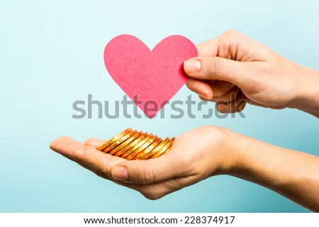 Hand showing red heart paper shape and coins on blue background. Love and money concept. - stock photo