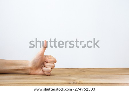 Hand showing thumbs up on wood table - stock photo