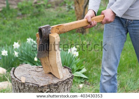 Hand slicing wood by axe - stock photo