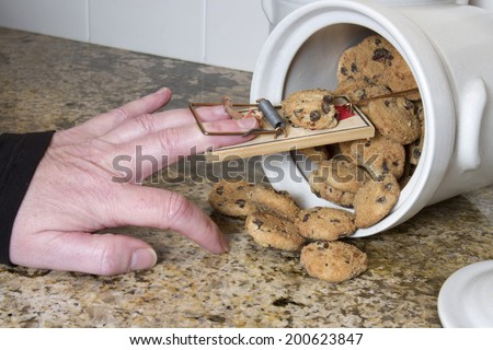 Hand stuck in a mousetrap after being tricked in the cookie jar - stock photo