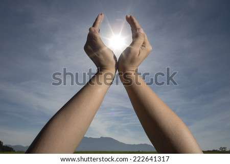 hand Sun and life / hand sun and blue sky showing freedom or solar power concept   - stock photo