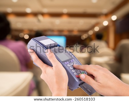 Hand Swiping Credit Card Machine with blurred people sitting rear at the business conference in background - stock photo