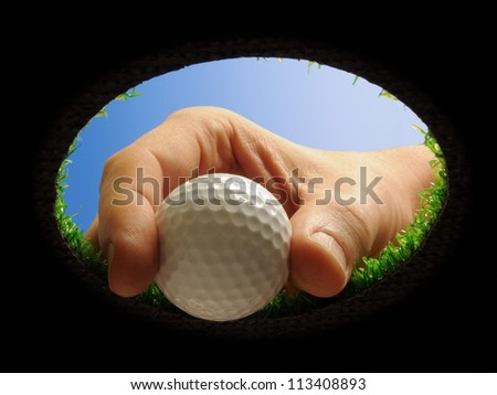 hand taking a golf ball out of a golf hole seen from below - stock photo