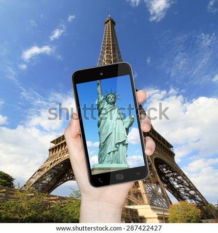 Hand taking a picture with mobile phone of the eiffel tower with statue of liberty on the screen - stock photo