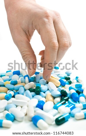 hand taking pills from the heap of different medications - stock photo