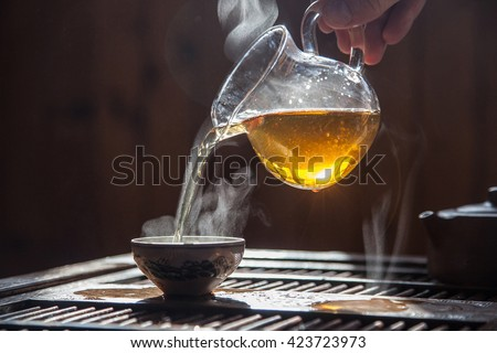 Hand that pours chinese green tea from glass kettle to smal cup - stock photo
