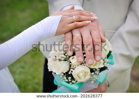 hand the bride and groom with rings on wedding bouquet - stock photo