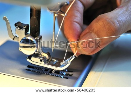Hand threading needle into sewing needle. For concepts such as fashion and design, work and industrial. - stock photo
