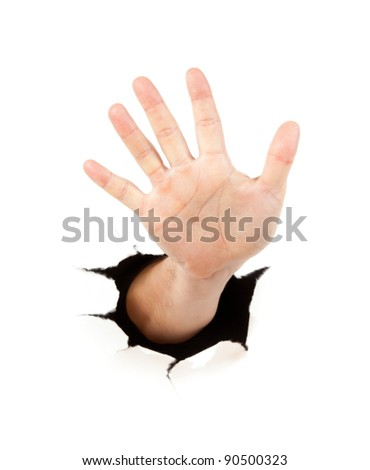 Hand through a hole in paper - stock photo
