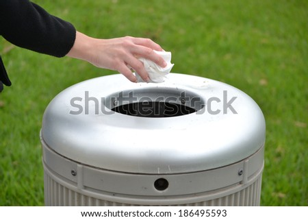 Hand throwing a paper in the trash - stock photo