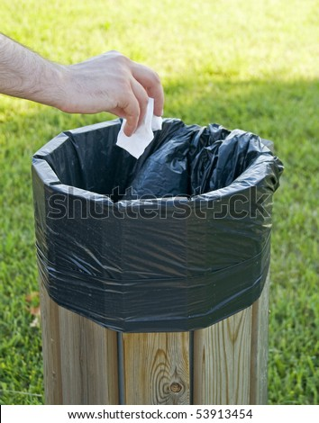 Hand throwing crumpled paper in the litterbin. - stock photo