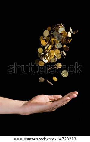 Hand throwing gold coins in the air - stock photo