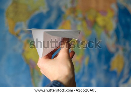 hand throwing paper plane in World map - stock photo