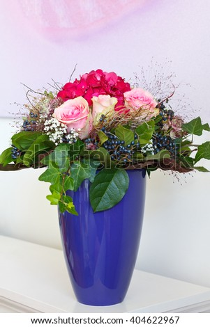 Hand tied bouquet of pink rose and purple hortensia flowers with berries, leaves and ivy in a blue vase, bright background, copy space, copyspace  - stock photo