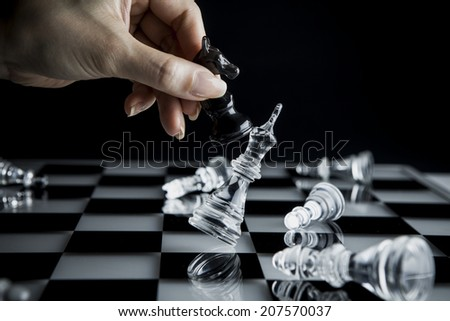 Hand to manipulate chess pieces - stock photo