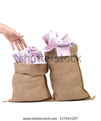 Hand to sacks with euro bills. Isolated on a white background. - stock photo