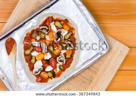 Hand tossed homemade vegetarian pizza topped with tomato paste and assorted fresh vegetables, mozzarella cheese and mushrooms ready to cook on a baking tray, overhead view - stock photo